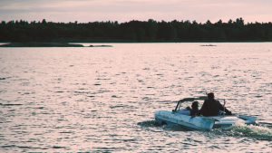 The founding partners Tim Keenleyside, Denzil Wadds, Mark Cohon driving a branded amphibious car trough the water