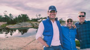 The founding partners, Tim Keenleyside, Denzil Wadds and Mark Cohon smiling with stunning granite rock and cool waters of Georgian Bay behind them