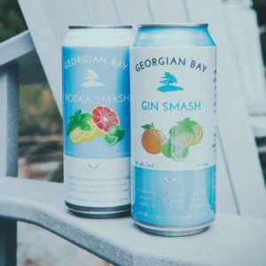 On the arm of a chair. Georgian Bay Gin Smash and Vodka Smash sit waiting for a happy consumer