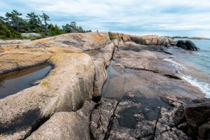 a Georgian Bay landscape showing clear skies, rocky shores and greenery. orange Lichen grows on the rocks