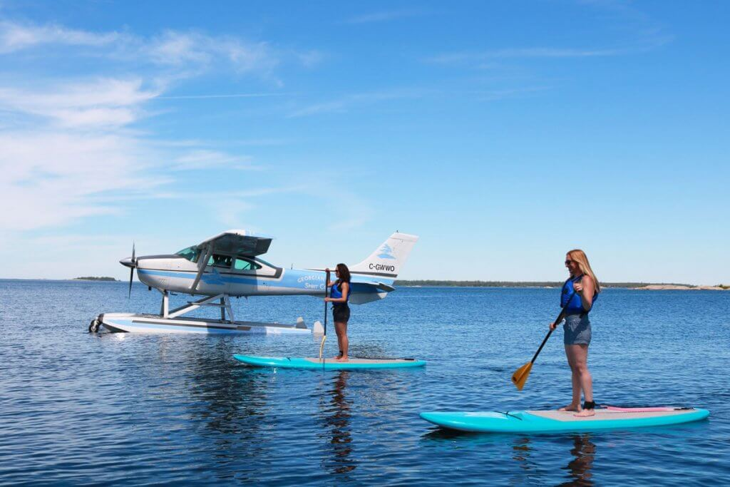 Two Paddle Boarders and a float plane on Georgian Bay