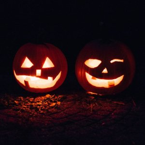 two pumpkins sit with carved faces in the dark