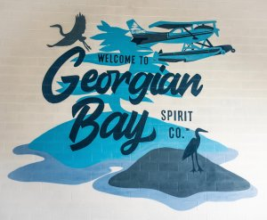 """A mural on a white Wall created with shades of blue that reads """"welcome to Georgian Bay Spirit Co."""